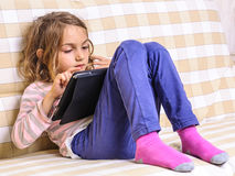 Little girl playing tablet home Stock Image