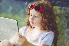 Little girl playing tablet pc on outdoors. Stock Photos