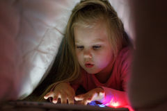 Little girl is playing on the tablet in secret from her parents at night under the blanket. Stock Image