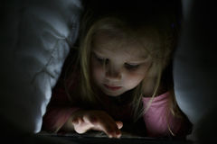 Little girl is playing on the tablet in secret from her parents at night under the blanket Royalty Free Stock Image