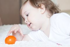 Little girl playing with tangerine Stock Images