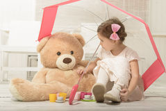 Little girl playing tea party sitting under an umbrella Royalty Free Stock Images