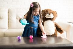 Little girl playing with a tea set stock photo
