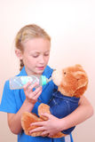 Little girl playing with teddy bear. A beautiful little Caucasian school girl playing with her cute teddy bear by pretending to feed it with a bottle Stock Images