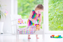 Little girl playing with a teddy bear Stock Photography