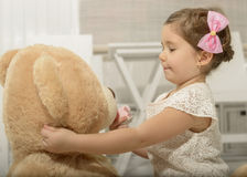 Little girl playing with teddy bear Royalty Free Stock Image