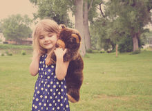 Little Girl Playing with Teddy Bear Friend in Park. A young girl is playing with a stuffed animal teddy bear on her back outside for a friendship or love concept royalty free stock photography