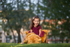 Little girl playing with a teddy bear in the park Royalty Free Stock Image