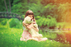 Little girl playing with teddy bear Stock Image