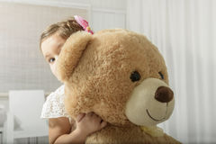 Little girl playing with teddy bear. Portrait of expressive little girl hugging huge plush bear, indoor shot on white room Stock Photos