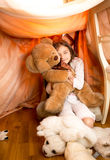 Little girl playing with teddy bear in self-made house Stock Photo