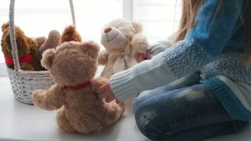 Little girl playing with teddy bears. Little cute girl playing with brown and white teddy bears, sitting on the floor stock footage