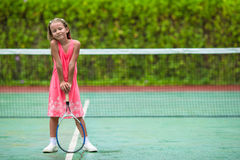 Little girl playing tennis on the court Stock Photography