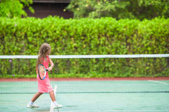Little girl playing tennis on the court Royalty Free Stock Photos