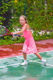Little girl playing tennis on the court Royalty Free Stock Images