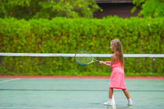 Little girl playing tennis on the court Royalty Free Stock Photography