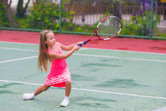 Little girl playing tennis on the court Stock Image