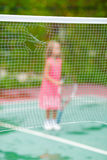 Little girl playing tennis on the court Stock Photos