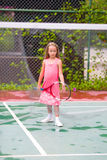 Little girl playing tennis on the court Royalty Free Stock Image