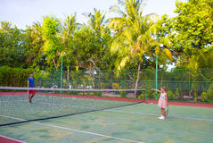 Little girl playing tennis with her dad on the Royalty Free Stock Images