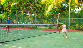 Little girl playing tennis with her dad on the Royalty Free Stock Photography