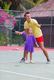 Little girl playing tennis with her dad on the Royalty Free Stock Image