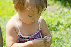 Little girl playing with toxic toadstool mushrooms Stock Images
