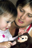 Little girl playing with toy. Mother attentively watching stock images