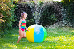 Little girl playing with toy ball garden sprinkler Royalty Free Stock Photos