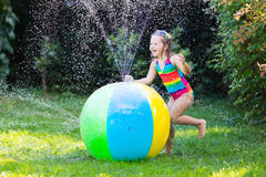 Little girl playing with toy ball garden sprinkler. Funny laughing little girl in a colorful swimming suit playing with toy ball garden sprinkler with water stock photos