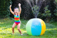 Little girl playing with toy ball garden sprinkler Stock Photo