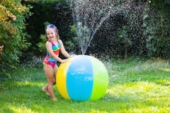 Little girl playing with toy ball garden sprinkler Royalty Free Stock Images