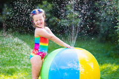 Little girl playing with toy ball garden sprinkler. Funny laughing little girl in a colorful swimming suit playing with toy ball garden sprinkler with water royalty free stock photography