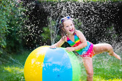 Little girl playing with toy ball garden sprinkler. Funny laughing little girl in a colorful swimming suit playing with toy ball garden sprinkler with water stock photography