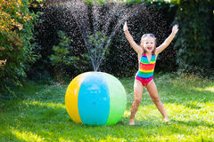Little girl playing with toy ball garden sprinkler Royalty Free Stock Image