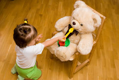 Little girl playing with a toy bear Stock Photo