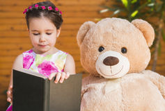 Little girl playing with toy bear outside Royalty Free Stock Images