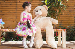 Little girl playing with toy bear outside Royalty Free Stock Image
