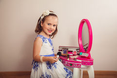 Little girl playing with the toy beauty table Royalty Free Stock Image