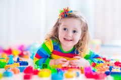 Little girl playing with toy blocks Stock Images