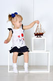 Little girl playing with toy boat in the studio Royalty Free Stock Image