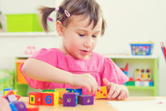 Little girl playing with toy bricks at school Royalty Free Stock Photo