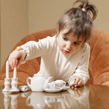 Little girl playing with toy dishware Stock Images