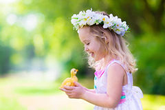 Little girl playing with a toy duck. Little girl having fun on Easter egg hunt. Kid in flower crown playing with toy duck or chicken. Children searching for eggs royalty free stock image