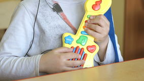 Little girl playing on toy guitar at kindergarten stock video