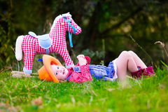 Little girl playing with toy horse in cowboy costume. Little girl dressed up as cowgirl playing with toy rocking horse in park. Kids play cowboy outdoors Stock Photography