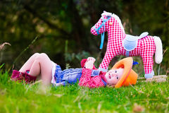 Little girl playing with toy horse in cowboy costume. Little girl dressed up as cowgirl playing with toy rocking horse in park. Kids play cowboy outdoors Royalty Free Stock Photos