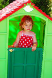 Little girl playing in toy house in the  garden Royalty Free Stock Photo
