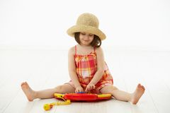 Little girl playing with toy instrument. Little girl sitting on floor playing with toy music instrument over white background Stock Photo