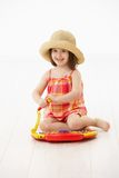 Little girl playing with toy instrument Royalty Free Stock Image